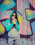 Stylish teenage girl in colorful sunglasses drinking juce near g Stock Photography
