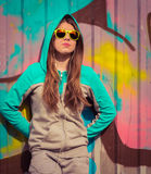 Stylish teenage girl in colorful sunglasses posing near fragment Stock Images