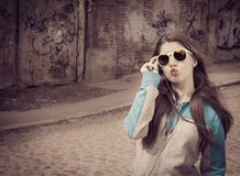 Stylish teenage girl in colorful sunglasses posing near graffiti Royalty Free Stock Images