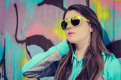 Stylish teenage girl in colorful sunglasses posing near graffiti Royalty Free Stock Photos