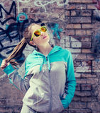 Stylish teenage girl in colorful sunglasses posing near graffiti Royalty Free Stock Photos