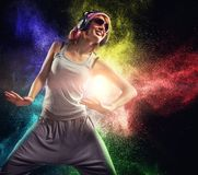 Stylish teenage girl with headphones. Dancing against colourful powder explosion Stock Photography