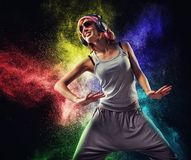 Stylish teenage girl with headphones dancing. Against colourful powder explosion Stock Photography
