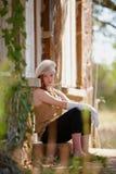 Stylish teenage girl sitting. Stylish teenage girl wearing knit hat and white gloves, sitting on building doorstep Stock Photos
