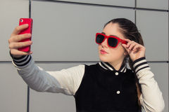 Stylish teenage girl taking self portrait with mobile phone Stock Photo