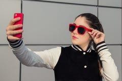 Stylish teenage girl taking self portrait with mobile phone Stock Photo