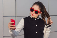 Stylish teenage girl taking self portrait with mobile phone Stock Photography