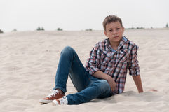 Stylish teenager on the beach. Stylish teenager sitting on the beach Stock Image