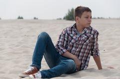 Stylish teenager on the beach. Stylish teenager sitting on the beach Royalty Free Stock Photo