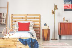 Stylish teenager bedroom interior with wooden bed and vintage furniture, real photo royalty free stock image
