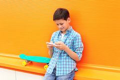 Stylish teenager boy with skateboard using phone in city Stock Images