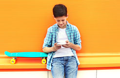 Stylish teenager boy with skateboard using smartphone in city Stock Photography