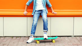 Stylish teenager boy wearing a checkered shirt and jeans on skateboard Stock Photos