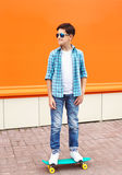 Stylish teenager boy wearing a checkered shirt, sunglasses on skateboard Stock Image