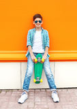 Stylish teenager boy wearing a checkered shirt, sunglasses and skateboard in city Stock Photo