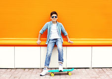 Stylish teenager boy wearing a checkered shirt, sunglasses on skateboard in city. Over orange background Royalty Free Stock Photos