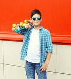 Stylish teenager boy wearing a checkered shirt and sunglasses with skateboard in city Stock Photography