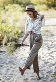 Stylish teenager girl walks barefoot in the sand Royalty Free Stock Images