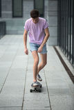 Stylish teenager riding a longboard Royalty Free Stock Images