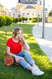 Stylish teenager weared in jeans and red T-shirt sitting on grass. stock photos