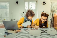 Cute stylish teens sitting near laptop and drawing sketches. Stylish teens. Cute stylish teens wearing glasses sitting near laptop and drawing sketches royalty free stock image
