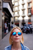 Stylish and tend female in urban setting looking to you. Portrait of cute hipster girl in summer sunglasses looking to the camera with copy space above her head royalty free stock photos