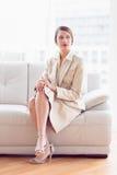 Stylish thoughtful businesswoman sitting on sofa Royalty Free Stock Image
