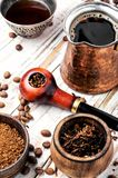 Smoking pipe and coffee. Stylish tobacco pipe with tobacco and brewed coffee royalty free stock photo