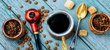 Smoking pipe and coffee. Stylish tobacco pipe with tobacco and brewed coffee royalty free stock photos