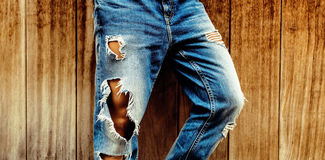 Stylish torn blue jeans on wooden background. unisex style Stock Photos