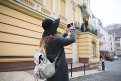 A stylish tourist girl takes a photo of the old town on his own smartphone. A stylish tourist girl makes a photo of the old town on his own smartphone. A woman Royalty Free Stock Image