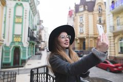 Stylish tourist girl takes selfie on the background of a beautiful old town. stock images