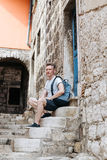 Stylish tourist. Man dressed in a white shirt and shorts with backpack over his shoulder. Sitting on the steps of European city. Stylish tourist. Man dressed in Stock Photography