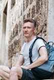 Stylish tourist. Man dressed in a white shirt and shorts with backpack over his shoulder. Sitting on the steps of European city Stock Images