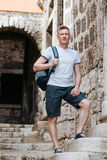 Stylish tourist. Man dressed in a white shirt and shorts with backpack over his shoulder. Standing on the steps of European city Stock Photos
