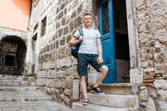 Stylish tourist. Man dressed in a white shirt and shorts with backpack over his shoulder. Standing on the steps of European city Stock Photo