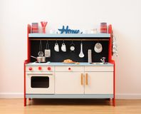 Stylish toy kitchen with oven, drawers, stove and sink equipped. With utensils ready to play front view stock photo