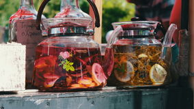 Stylish transparent beautiful teapot with herbal infusion and lemon inside. Street food. Cafe in the open air. Food fair stock video footage