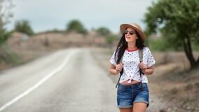 Stylish woman in straw hat and trendy sunglasses walking on highway. Shot with RED camera in 4K