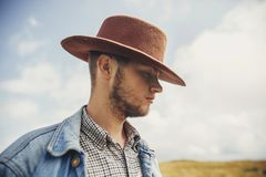 Stylish traveler bearded man in hat standing on top of sunny mou. Ntains in clouds. space for text. hipster cowboy guy portrait. amazing atmospheric moment Royalty Free Stock Images