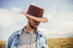 Stylish traveler bearded man in hat standing on top of sunny mou. Ntains in clouds. space for text. hipster cowboy guy portrait. amazing atmospheric moment Stock Images