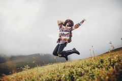 Stylish traveler girl in hat with backpack jumping in mountains. Royalty Free Stock Photo