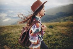 Stylish traveler girl in hat with backpack walking in mountains. Hipster woman exploring on top of mountain. space for text. wanderlust and travel concept Royalty Free Stock Photos