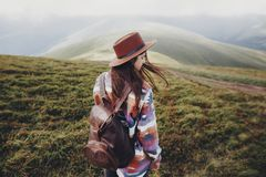 Stylish traveler girl in hat with backpack walking in mountains. Hipster woman posing on top of windy mountain. space for text. wanderlust and travel concept Royalty Free Stock Photo