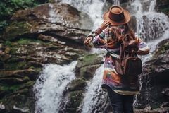 Stylish traveler girl in hat looking at waterfall, exploring woo. Ds. hipster woman with backpack travelling, holding hat at river in forest. space for text Stock Images
