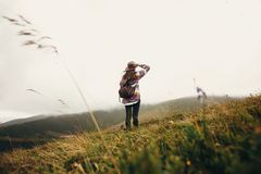 Stylish traveler girl holding hat with backpack and windy hair i. N mountains clouds. summer vacation. travel and wanderlust concept. space for text. back view stock image