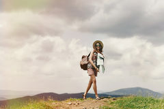 Stylish traveler hipster woman  with backpack holding map and la Stock Photography