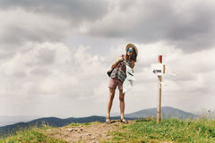 Stylish traveler hipster woman  with backpack holding map and la. Ughing on top of mountains and sky, travel  concept, space for text Stock Images