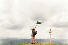 Stylish traveler hipster woman with backpack holding map into s. Ky on top of mountains , travel concept, space for text, back view stock photo