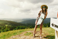 Stylish traveler hipster woman  with backpack holding map and sm. Iling on top of mountains and sky, travel concept, space for text Stock Photos